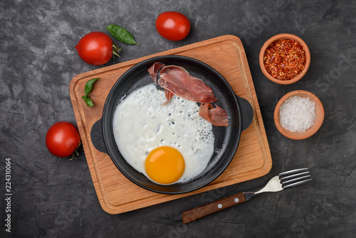 Fried egg in a pan with bacon and tomatoes on black background, top view.