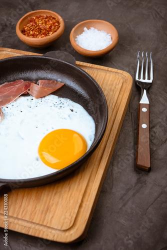 Staande foto Gebakken Eieren Fried egg in a pan with bacon and tomatoes on black background.