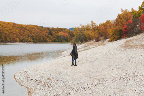 Fotografiet  Young brunette woman wearing grey poncho walking alone near the lake in autumn