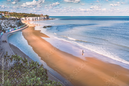 Fényképezés  Low tide at Stone Bay, Broadstairs, Kent as summer turns to autumn, a lone surfer walks on the beach and a family on the promenade along side the beach huts and white cliffs