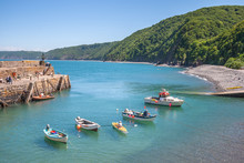Fishing Boats In The Harbour At Clovelly, Charming Fishing Village On The Atlantic Ocean Coast, Devon, England