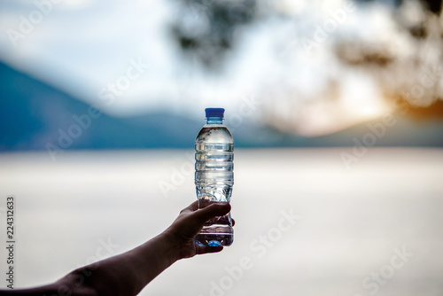 Fotografía  Girl holding a bottle of drinking water at sunset