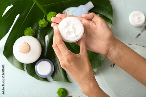Fototapeta  Woman holding jar of natural cream, top view