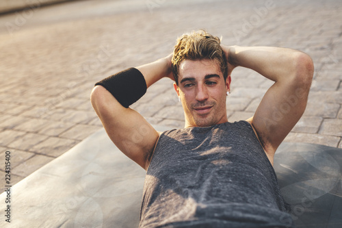 Portrait of young break dancer lying down in the park at sunset