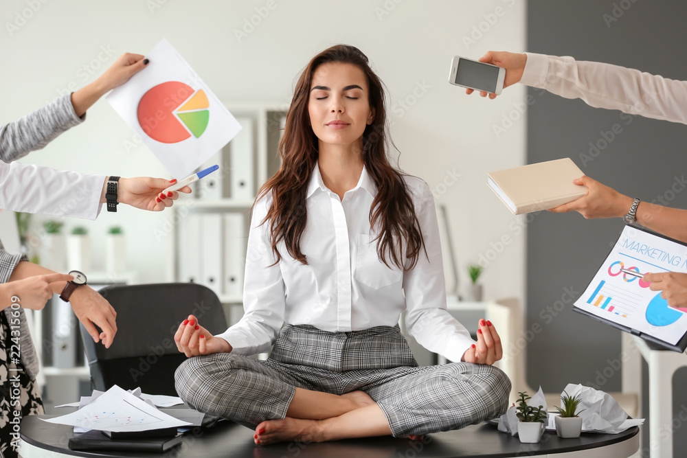 Fototapeta Businesswoman with a lot of work to do meditating in office