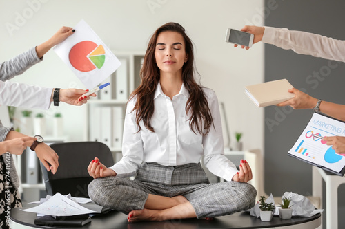 Ingelijste posters Zen Businesswoman with a lot of work to do meditating in office