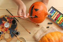 Woman Painting Pumpkin For Halloween Party On Wooden Table