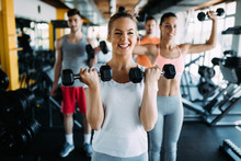 Young Woman Doing Exercise With Dumbbell In Gym