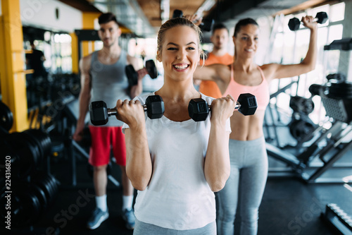 Poster Fitness Young woman doing exercise with dumbbell in gym