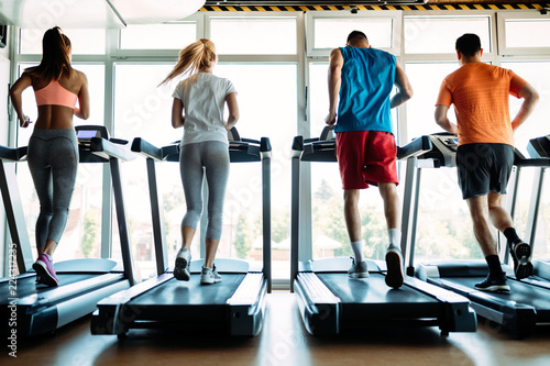 Poster Fitness Happy people on treadmills in the gym