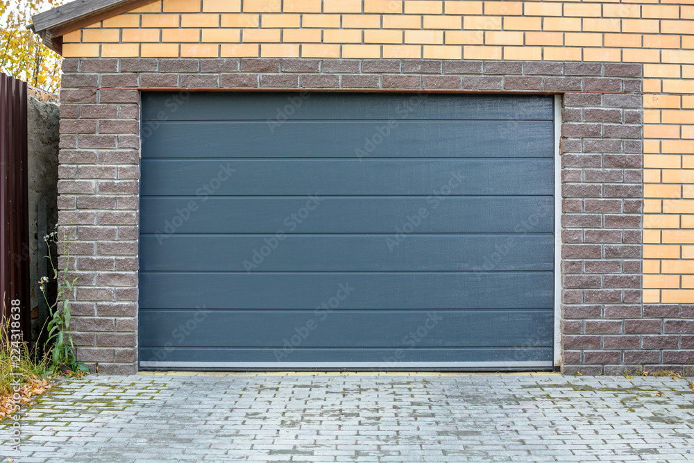 Fototapeta Automatic garage gate. Access to a brick garage for a car with a dark door