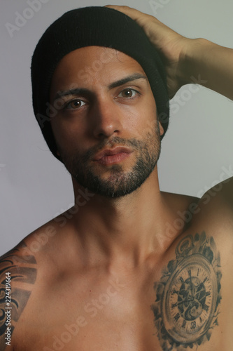 Pinturas sobre lienzo  sexy male tattooed wearing a black hat on gray background
