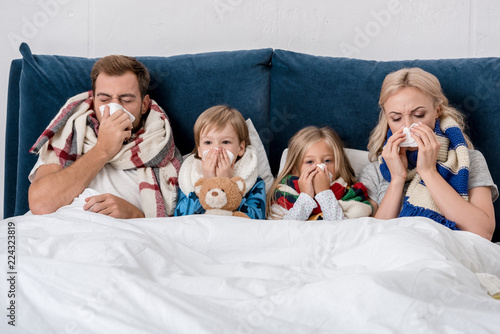 sick young family blowing noses with napkins together while lying in bed Fototapeta