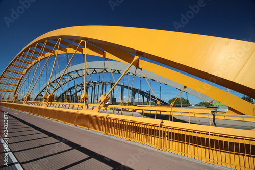 Fotografie, Obraz  Bright yellow bridge named Hogeweidebrug over the Amsterdam-Rhine canal in Utrecht for traffic and Vleutenspoorbrug which is a trainbridge