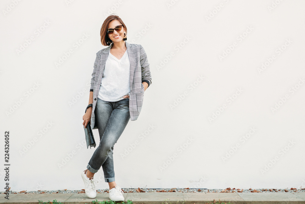 Fototapeta Smiling woman posing in casual city outfit in black and gray colors