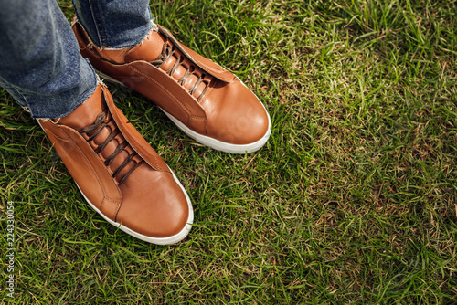 Fotografia  cropped image of man in jeans and brown shoes standing on green grass in park