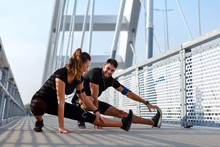 Young Couple Doing Morning Workout Outdoors. Young Man And Woman Stretching They Muscle Before Running On Bridge.