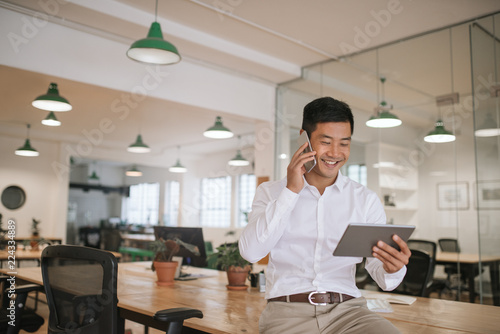 Fotografie, Obraz  Asian businessman talking on his cellphone and holding a tablet