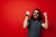 Cheerful bearded man with long curly hair wearing sunglasses and celebrating over red background