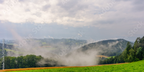Color rural foggy summer panoramic landscape image of an idyllic farmland countryside with clouds in the sky and a downhill view over fields, forest,rolling hills and valleys towards the horizon