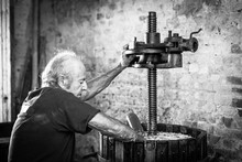 Senior Winemaker Farmer Working On A Traditional Wine Press. Winery Background, Black And White Picture