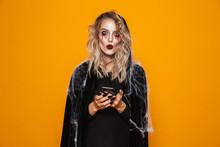 Excited Woman Wearing Black Costume And Halloween Makeup Holding Mobile Phone, Isolated Over Yellow Background