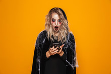 Attractive Wizard Woman Wearing Black Costume And Halloween Makeup Holding Mobile Phone, Isolated Over Yellow Background