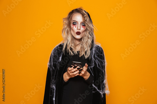 Fényképezés Excited woman wearing black costume and halloween makeup holding mobile phone, i
