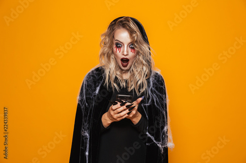 Fotografia Attractive wizard woman wearing black costume and halloween makeup holding mobil