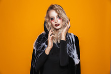 Scary Wizard Woman Wearing Black Costume And Halloween Makeup Looking At The Camera, Isolated Over Yellow Background