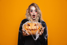 Magician Woman Wearing Black Costume And Halloween Makeup Holding Carved Pumpkin, Isolated Over Yellow Background