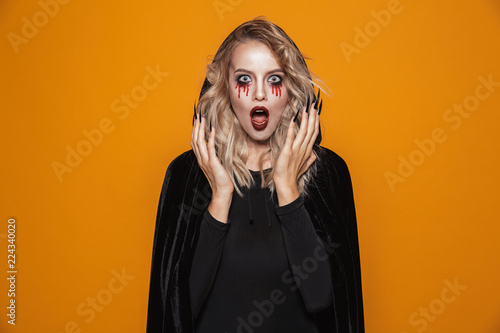 Fototapeta  Scary woman wearing black costume and halloween makeup looking at the camera, is