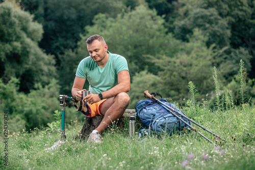 Fotografiet  Delighted male tourist with prosthesis resting outdoors