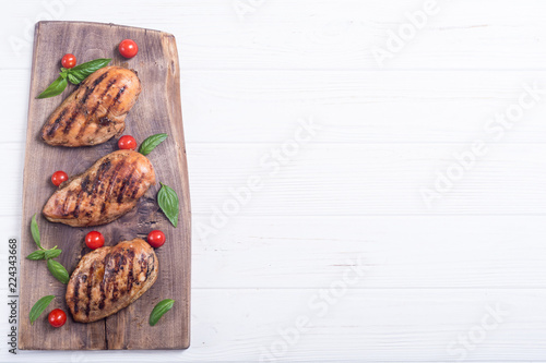 Grilled chicken breast ( fillet ) with basil and tomatoes