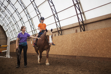 Boy in helmet learning Horseback Riding with instructor