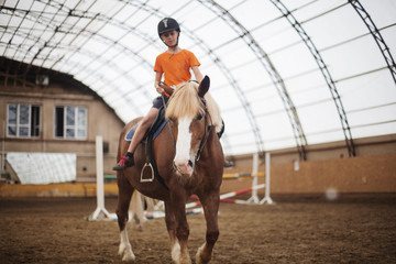 Boy in helmet learning Horseback Riding