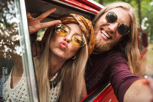 Photo of kind hippie couple smiling, and showing peace sign while driving retro фототапет