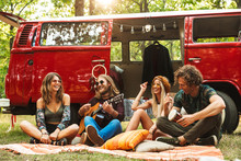 Group Of Friends Hippies Men And Women Laughing, And Playing Guitar Near Vintage Minivan Into The Nature