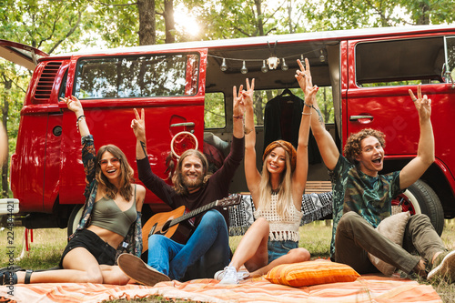 фотография Group of friends hippies men and women rejoicing, and sitting near vintage miniv