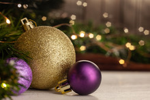 Christmas Toy Golden Ball Next To A Purple Ball With A Pattern On A Light Table In The Background A Christmas Tree With A Garland Next To A Wooden Wall.