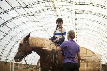 Teen girl in helmet learning Horseback Riding