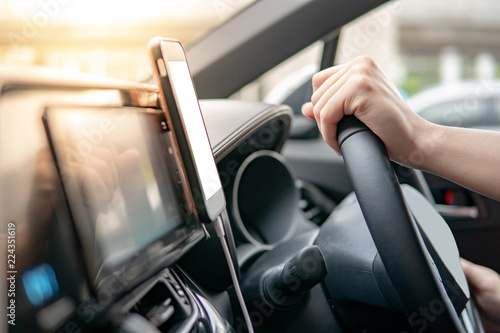 Male driver hand holding on steering wheel using smartphone for GPS navigation. Mobile phone mounting with magnet on the car console in modern car. Urban driving lifestyle with mobile app technology