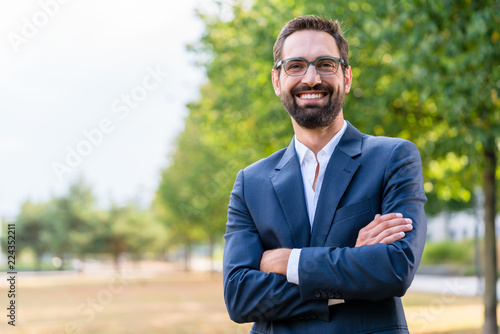 Photographie  Portrait of confident businessman with crossed arms standing in the park