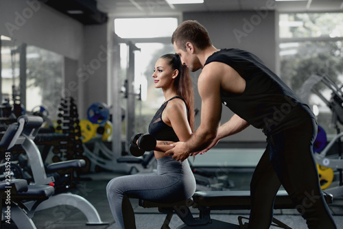 Handsome personal instructor helping his female client to training with dumbbells Fototapet