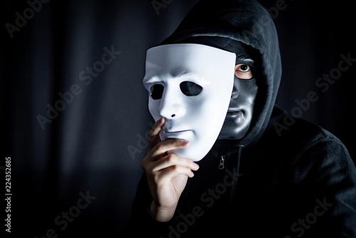 Photographie Mystery hoody man wearing black mask holding white mask