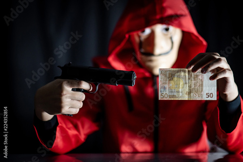Mystery man wearing mask and red hoodie holding gun showing euro banknote in his hand Fototapet