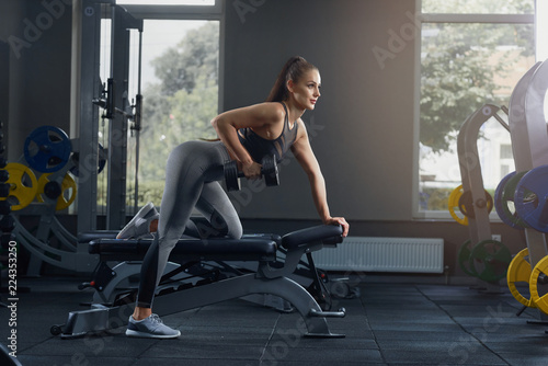 Foto  Sexy athletic woman pumping up muscles with dumbbells at gym.