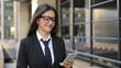 Beautiful businesswoman on urban street and using smartphone app. Steadicam shot, slow motion