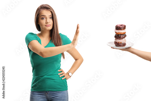 Young woman refusing a plate of donuts Fototapeta