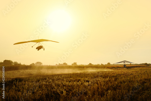 Two hang gliders tow on the sunset